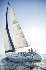 Friends traveling on sailboat in sea