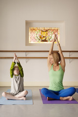 Boy (6-7) doing yoga with woman