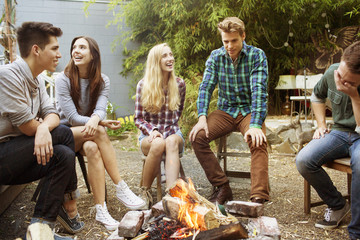 Teenage girl (16-17) laughing with her friends by campfire