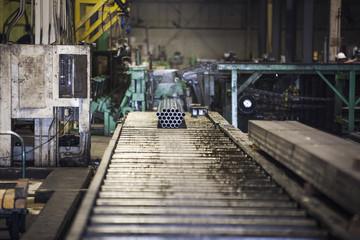 Bundle of steel pipes moving on conveyor belt