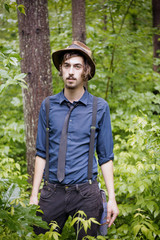 Portrait of man in hat and suspenders in forest