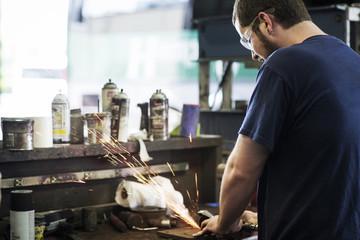 Mechanic grinding metal in workshop