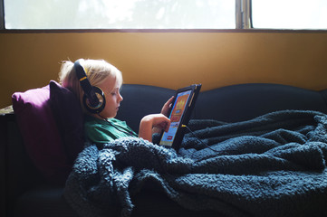 Boy (6-7) listening to music on headphones, using digital tablet
