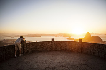 Man photographing seaside sunrise from observation point