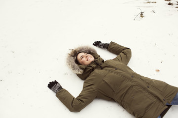 Woman lying in snow smiling