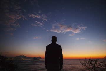 Silhouette of man by sea at sunrise