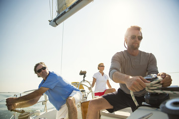 Man adjusting ropes while traveling with friends in yacht
