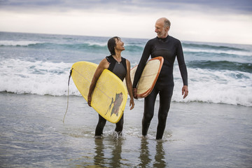 Happy couple with surfboards talking while walking on shore at beach