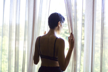 Woman looking outside through bedroom curtains
