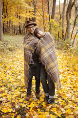 Couple wrapped in blanket in autumn forest
