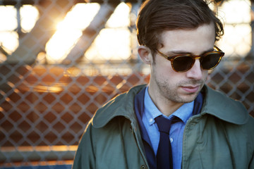 Man with sunglasses standing at pedestrian walkway of Manhattan Bridge