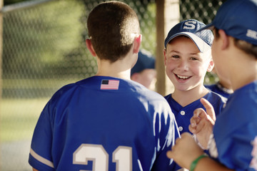 Portrait of smiling baseball player with friends in dugout