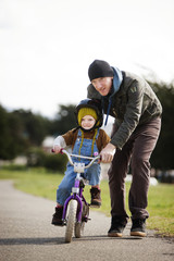 Father teaching his son (4-5) how to ride bike