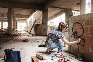 Woman spraying graffiti on building wall