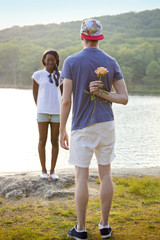 Man hiding rose behind his back for his girlfriend