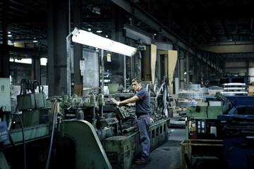 Man operating machinery in factory
