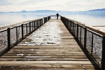 Man standing at edge of snowy pier