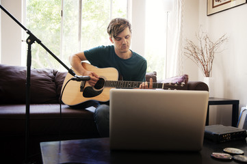 Young man playing guitar in living room