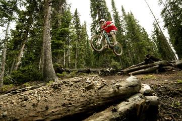 Biker jumping logs