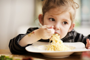 Girl looking away while eating noodles at table in home
