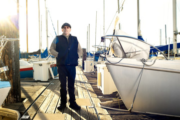 Old man standing near boats