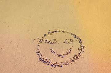 Top view on happy smiley face drawing on a sand.