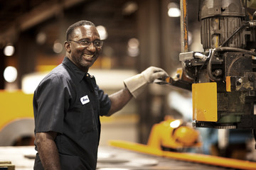 Smiling mature worker using machinery in factory