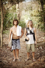 Two male friends standing in jungle path