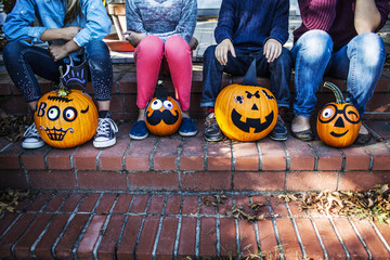 Low section of family sitting with decorated pumpkins on steps during Halloween