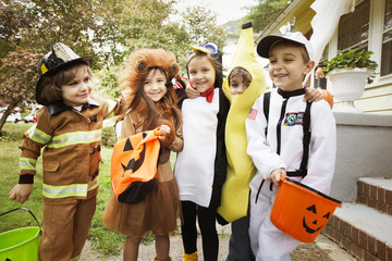 Happy children in Halloween costumes standing in yard during trick or treating