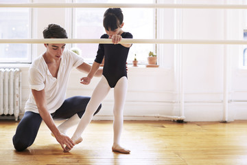Male ballet instructor instructing ballerina in studio