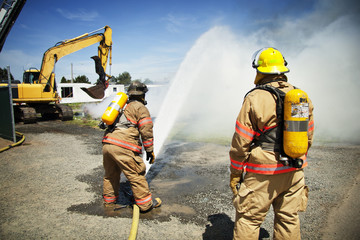 Rear view of firefighters spraying water with fire hose