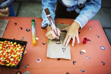 Midsection of girl decorating paper bag at table during Halloween party