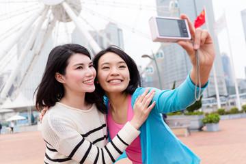 Two girls taking self image by digital camera