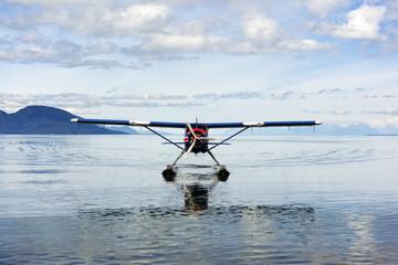 Seaplane in sea against cloudy sky