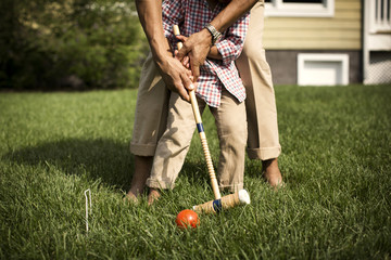 Low section of father and son playing croquet in backyard