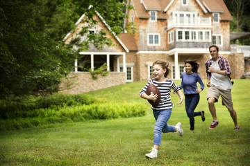 Family playing rugby in lawn