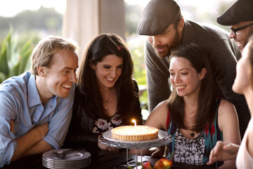 Happy friends looking at birthday cake