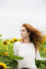 Woman looking away while standing in sunflower farm