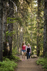 Happy mother and daughter walking on pathway amidst trees at forest
