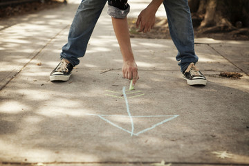 Low section of man drawing arrow symbol on footpath