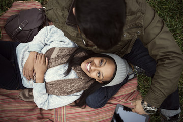 High angle view of happy woman relaxing on boyfriend's lap in park