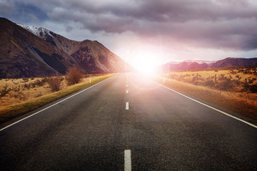 beautiful sun rising sky with asphalt highways road against snow
