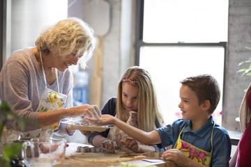 Children with grandmother preparing cookies in kitchen