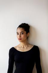 Portrait of confident ballet dancer standing against wall in ballet studio