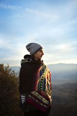 Man wrapped in shawl looking away while standing against sky