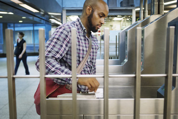 Man swiping smart card at railroad entrance