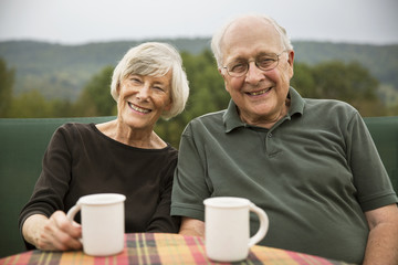 Portrait of smiling senior couple sitting at table in lawn