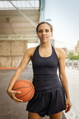 Portrait of young woman standing on basketball court