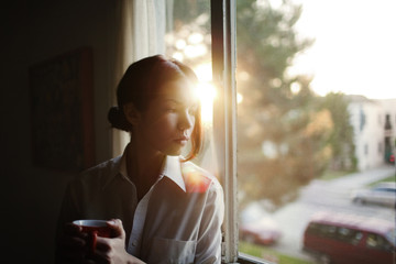 Woman looking away while sitting by window at home